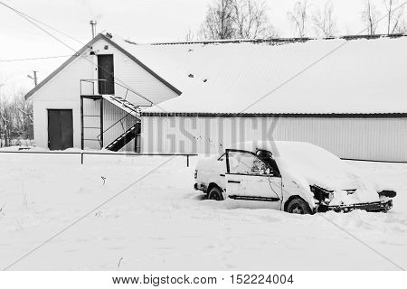 Abandoned car in snow near abandoned houses in black and white