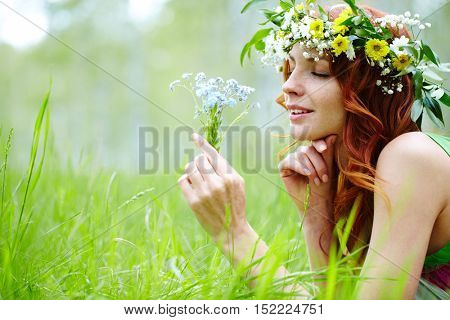 Portrait of a young girl lying on grass and holding wildflowers
