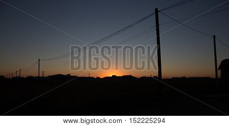 Poles with wires on a background of blue sky at sunset in summer