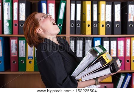 Business Lady holding large Stack of Office Folders casual Clothing Dress Code young beautiful face Cupboard with many Documents Files of different colors