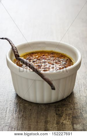 Traditional French creme brulee dessert with caramelized sugar on top, on wooden table
