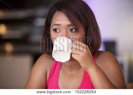 closeup of beautiful hispanic woman drinking coffee