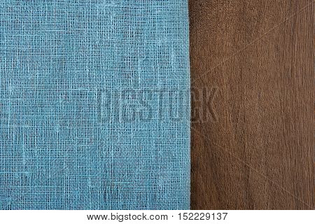 Sackcloth from left side wooden table. Soft blue woven linen fabric texture / wood texture. Coarse jute sack.  Top view background.