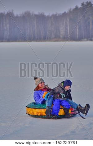 Happy Mother and her little son enjoying sleigh ride in Russian winter holiday