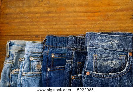 Blue jeans on a brown wooden background and Blue jeans denim Collection jeans