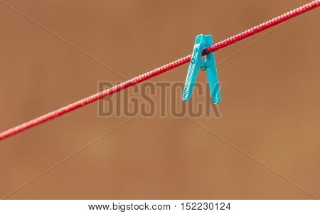 Blue clip on a  red string representing uniqueness