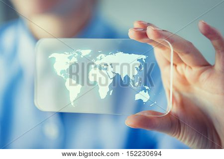 business, technology, international communication, mass media and people concept - close up of woman hand holding and showing transparent smartphone with world map on screen