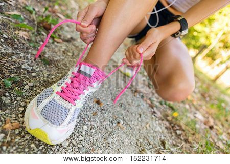 Unrecognizable Woman Tying Shoelaces In The City Park.