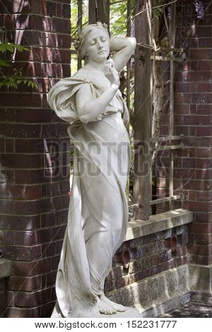 The sculpture of a girl standing in Auckland city botanical garden (New Zealand).