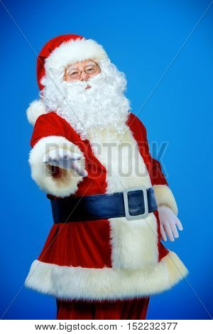 Portrait of a friendly traditional Santa Claus stretching his hand for a handshake. Studio shot over blue background. Christmas.