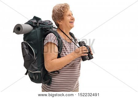 Mature female hiker holding a binoculars and looking in the distance isolated on white background