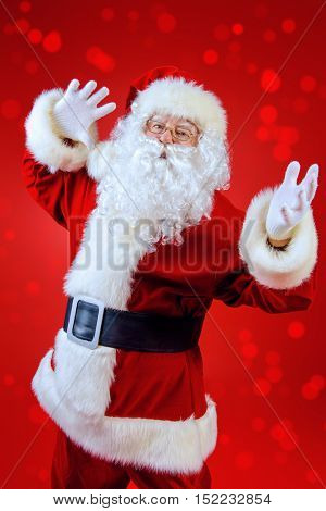 Santa Claus spreads his arms to the sides, expressing joy and surprise. Red background. Studio shot. Christmas.
