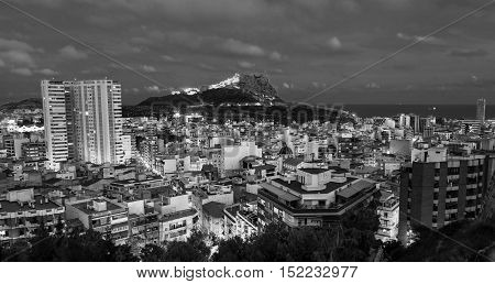 Aerial night view of Alicante Costa Blanca Spain. Old city center with harbor illumination. Santa Barbara Castle located on Mount Benacantil. Black and white
