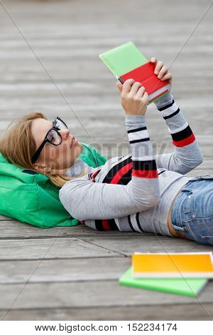 Girl spectacled looks at Tablet lying on wooden floor