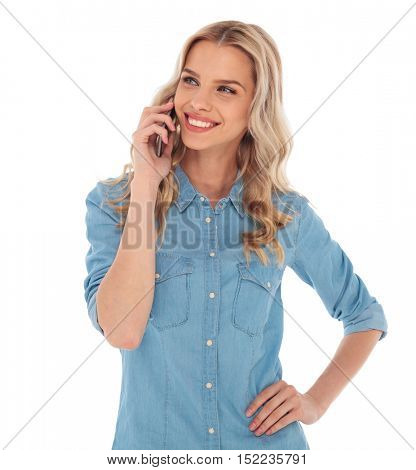 smiling young blond woman talking on the phone is looking to side on white background