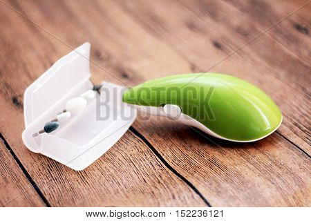 electric manicure set green plastic object wooden background