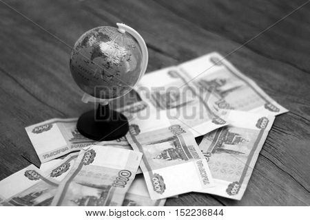 Russian money and the globe on wooden background