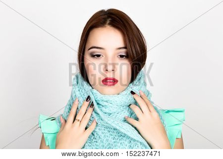 close-up portrait of a beautiful woman in a woolen scarf.