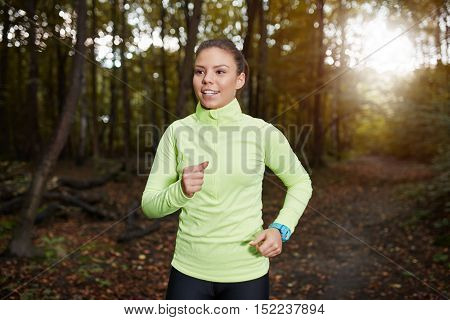Beautiful sportswoman jogging through the autumn forest