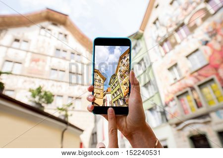 Photographing with smart phone old colorful buildings in the old town of Lucerne city in Switzerland