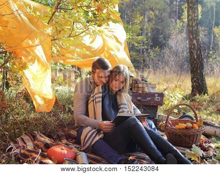 married couple in the autumn park on a picnic read the book