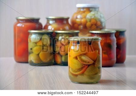 Bank with yellow tomatoes on the wooden floor in the foreground. Many inverted glass jars with canned pickled vegetables in the background.