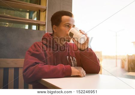 Close up portrait of a young man relaxing and drinking coffee in the city. Guy in the red shirt