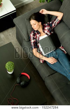 Attractive brunette girl sleeping on the sofa. Relaxed at home