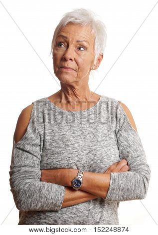 unsmiling mature woman with arms folded looking away. isolated on white.