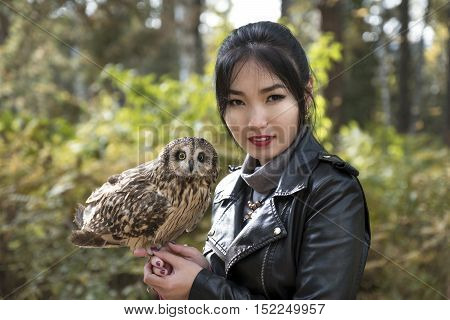 Portrait of an Asian girl with an owl sitting on the arm in the street in a black jacket in autumn