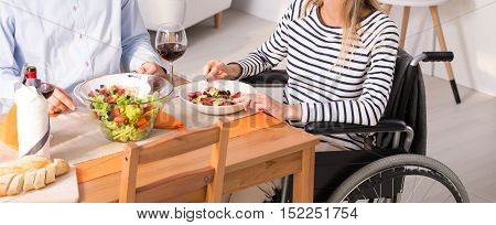 Woman Sitting At The Table On A Wheelchair During The Meal