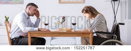 Man Sitting At The Table In Front Of His Wife On A Wheelchair