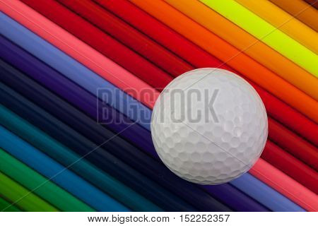 Detail of rainbow colorful pencil and golf ball on the table
