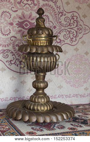 Vintage copper hookah in front of carpet