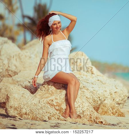 Young fashion woman in white relax on the beach stones. Happy tropical lifestyle. White sand, blue sky and crystal sea of beach. Vacation at Paradise. Ocean beach relax, travel