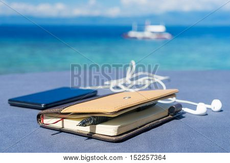 Closed notepad, pen and phone with headphones against tropical sea under cloudy sky at not sunny day