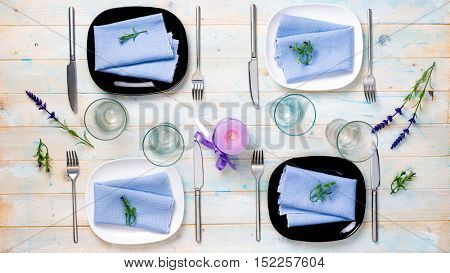 beautiful table serving for four with purple candle and flowers on wooden background, top view