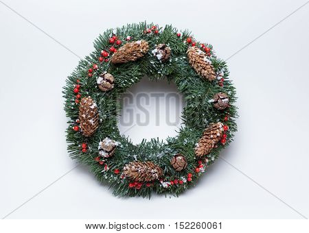 Christmas wreath of fir branches decorated with ilex, cypress cones, pine cones and artificial snow on white background