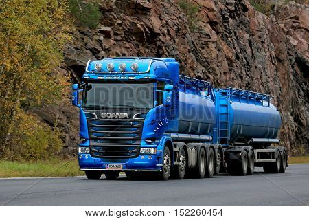 KARJAA, FINLAND - OCTOBER 15, 2016: Metallic blue Scania R580 tank truck moves along highway in autumn background of rock face.
