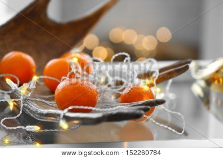 Mandarins with garland lights on table in decorated room