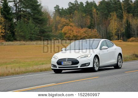 KAARINA, FINLAND - OCTOBER 16, 2016: White Tesla Model S electric car travels at speed along autumnal highway in South of Finland.