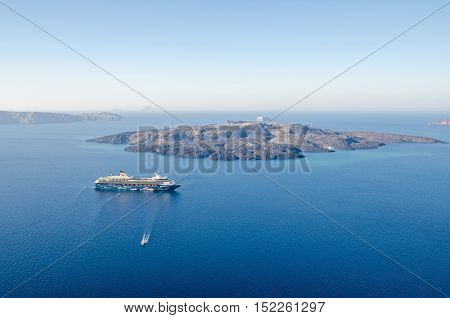Thira Greece - November 10 2015: Cruise liner Mein Schiff 2 anchored in tender harbor between the island Santorini and the uninhabited island of Nea Kameni in the Aegean Sea as seen from Thira.