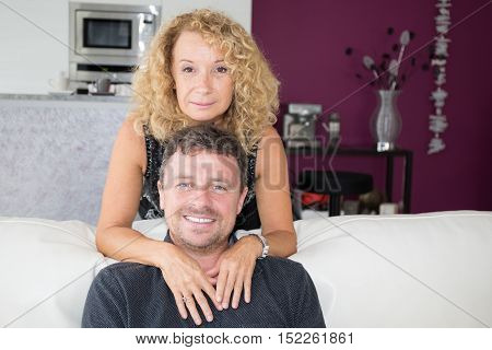 Smiling Middle Aged Couple Sitting On Couch In Living Room