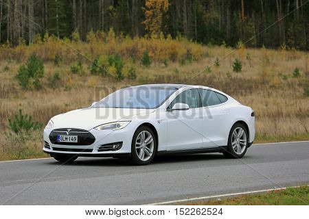 PAIMIO, FINLAND - OCTOBER 16, 2016: White Tesla Model S electric car travels along road through autumn scenery in South of Finland.