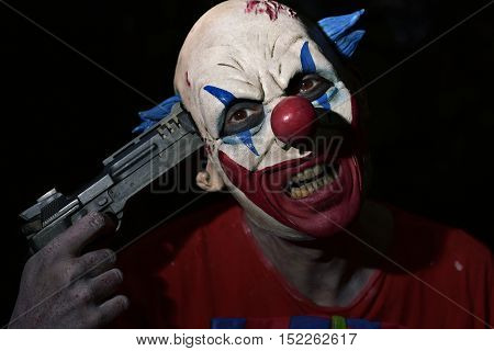 closeup of a scary evil clown pointing a gun to his own temple in the darkness