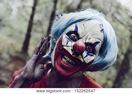 closeup of a scary evil clown in the woods touching his blue hair and smiling