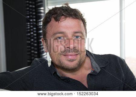 Happy Man Sitting On His Sofa Smiling At Camera