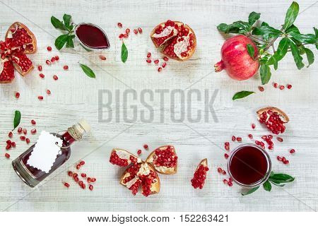 Pomegranate on a branch with leaves, broken pomegranates, seeds, leaves, gravy boat, bottle of sauce on a light wooden background. Pomegranate fruits, seeds and sauce. Horizontal. Top view.