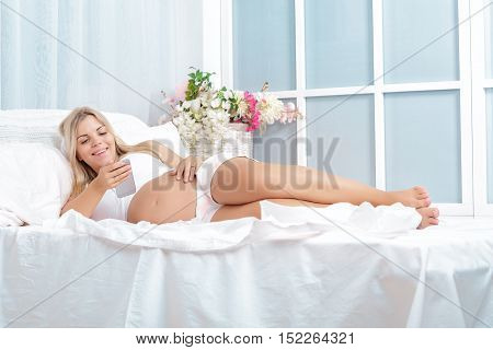 Pregnant blonde woman using her smart phone at home lying on bed