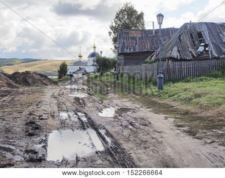 road mud puddles the Church of Constantine and Helena old wooden houses fence